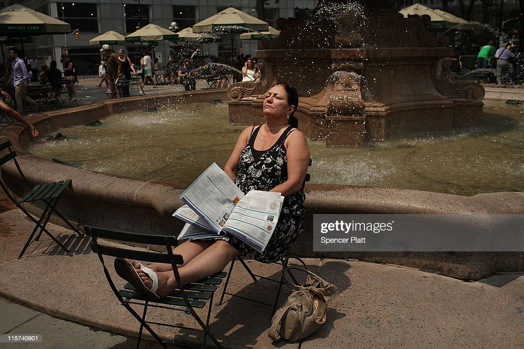 A woman takes a break in Bryant Park during a heat wave on June 9, 2011 in New York City. With the high today in Central Park expected to reach 99 degrees, a 78-year-old record is set to be broken. Some schools have been let out early due to the heat and Manhattan has opened cooling stations throughout the city. Temperatures are expected to drop into the mid-70s by tomorrow.