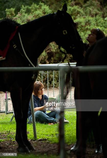 A woman takes a break in the paddock area at the Cartier International Polo day at Guards Polo Club in Windsor on July 25 2010 The Cartier...