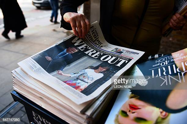 A woman takes a copy of the London Evening Standard with the front page reporting the resignation of British Prime Minister David Cameron and the...