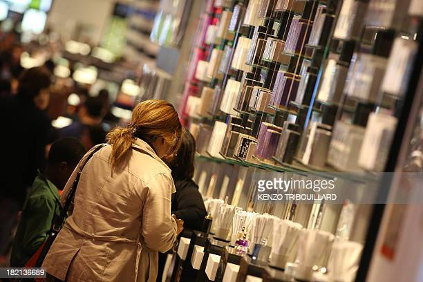 A woman takes a look at products on September 28 2013 in the flagship Paris store of French cosmetics maker 'Sephora' during night on the...