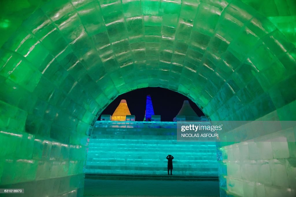A woman takes a photo as she visits ice sculptures illuminated by coloured lights at the Harbin Ice and Snow Festival to celebrate the new year in Harbin on January 5, 2017. / AFP / NICOLAS