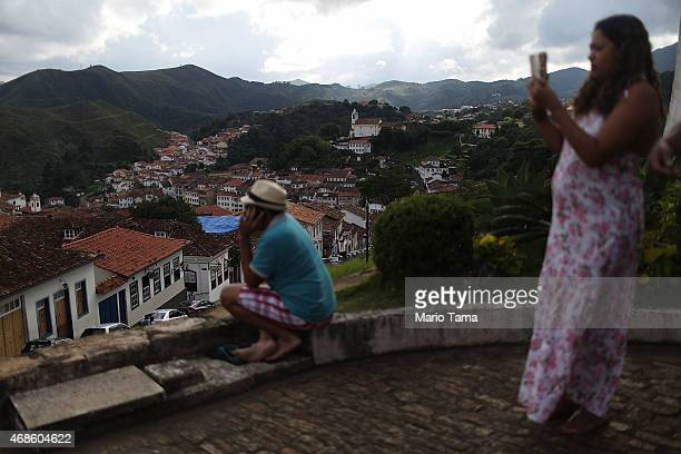 A woman takes a photo during traditional Semana Santa festivities on Good Friday on April 3 2015 in Ouro Preto Brazil Holy Week marks Easter...