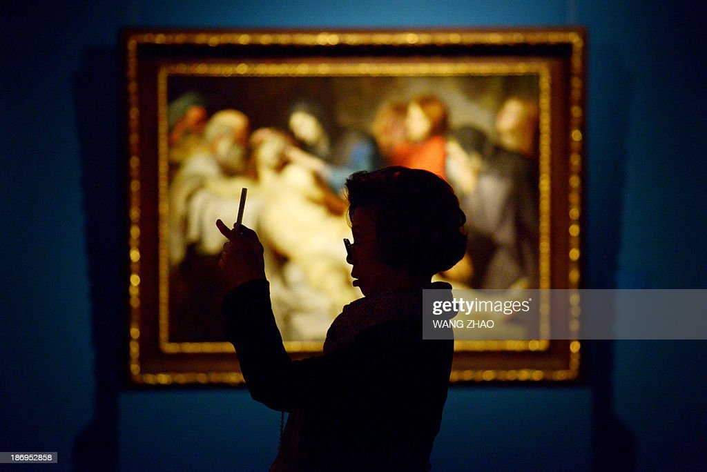A woman takes a photo in front of Peter Paul Rubens' 'The Lamentation' as she visits an exhibition at China's National Museum in Beijing on November 5,2013. Royal collections of Liechtenstein, including works by Rubens, Van Dyck and other Flemish painters, are being held at China's National Museum from November 5, 2013 to February 15, 2014.