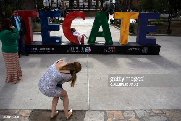 A woman takes a photo of a girl on a Tecate sign in Tecate northwestern Mexico on February 14 northwestern Mexico this image is part of an ongoing...
