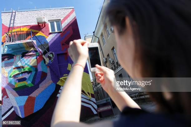 A woman takes a photo of a graffiti featuring Portugal's player Cristiano Ronaldo in central Kazan Russia on June 22 2017
