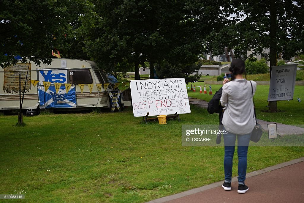 A woman takes a photo of a protest camp of people calling for a second referendum on Scottish independence, in Edinburgh, Scotland on June 25, 2016, following the pro-Brexit result of the UK's EU referendum vote. The result of Britain's June 23 referendum vote to leave the European Union (EU) has pitted parents against children, cities against rural areas, north against south and university graduates against those with fewer qualifications. London, Scotland and Northern Ireland voted to remain in the EU but Wales and large swathes of England, particularly former industrial hubs in the north with many disaffected workers, backed a Brexit. / AFP / OLI