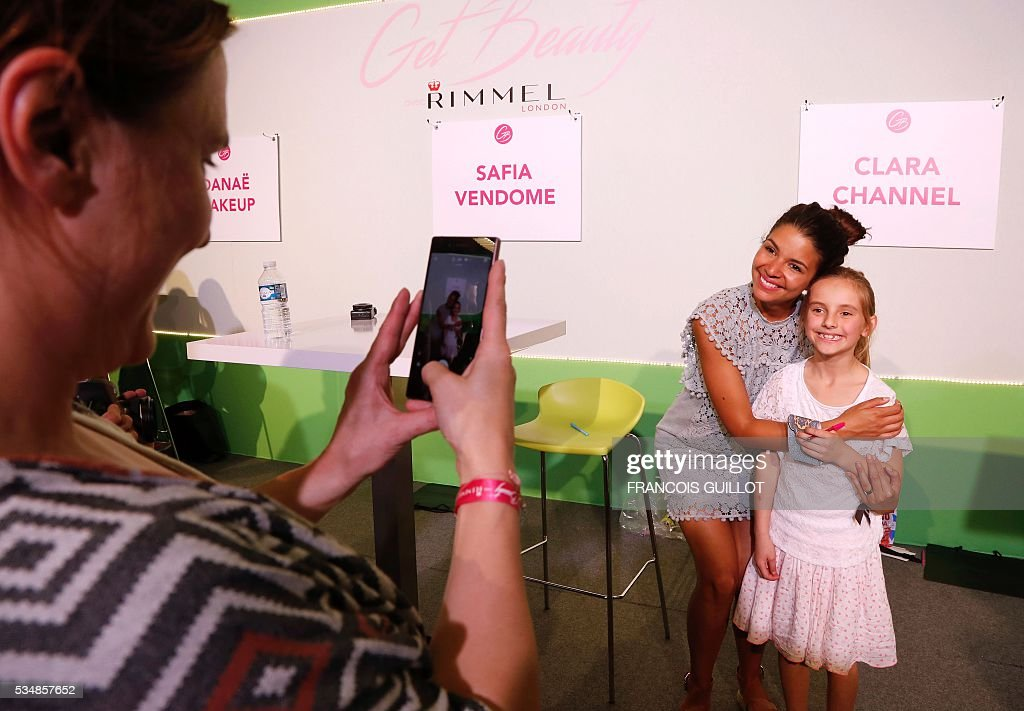 A woman takes a photo of French YouTube personality Safia Vendome posing with a girl during the Get Beauty fair, a beauty and fashion fair inspired by the US 'Beautycon' event gathering of fashion bloggers and YouTube personalities, on May 28, 2016 at the Vincennes' parc floral, eastern Paris. / AFP / FRANCOIS