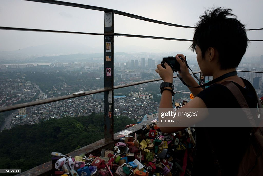 A woman takes a photo of the Seoul city skyline during heavy rain on July 2, 2013. July marks the wet season for Seoul during which the city of10 million people receives some 60 percent of its annual rainfall. AFP PHOTO / Ed Jones