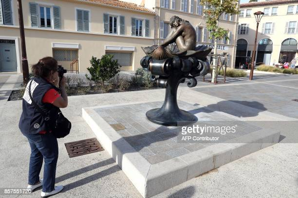 A woman takes a photo of the statue of French actress Brigitte Bardot based on an illustration watercolour by Italian illustrator Milo Manara at the...