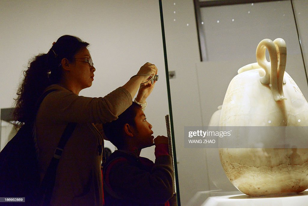 A woman (L) takes a photo standing behind a boy as he draws in front of a of big alabastron at the Collections of the Muse du Louvre exhibition at China's National Museum in Beijing on November 5, 2013. The Mediterranean World from the Collections of the Muse du Louvre is on display at the China National Museum in Beijing from October 29, 2013 to February 10, 2014.