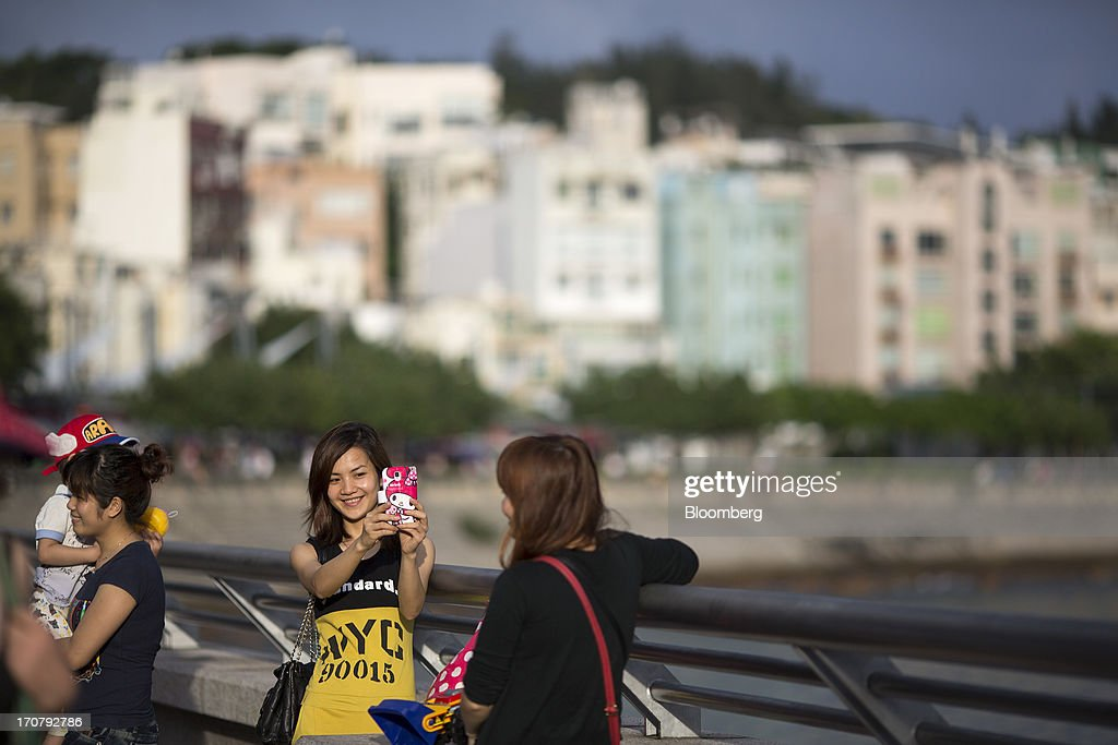 A woman takes a photo with a mobile device on the waterfront in the Stanley area of Hong Kong, China, on Sunday, June 16, 2013. A shortage of housing, low mortgage costs and a buying spree by mainland Chinese have led home prices to more than double since the beginning of 2009, shrugging off repeated attempts by the government to curb gains amid an outcry over affordability. Photographer: Jerome Favre/Bloomberg via Getty Images