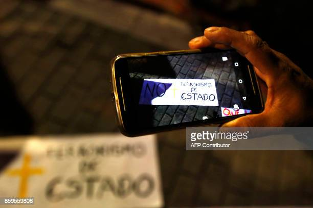 A woman takes a photo with her cell phone of a sign reading 'no more state terrorism' during a candlelight vigil to honor farmers killed during an...
