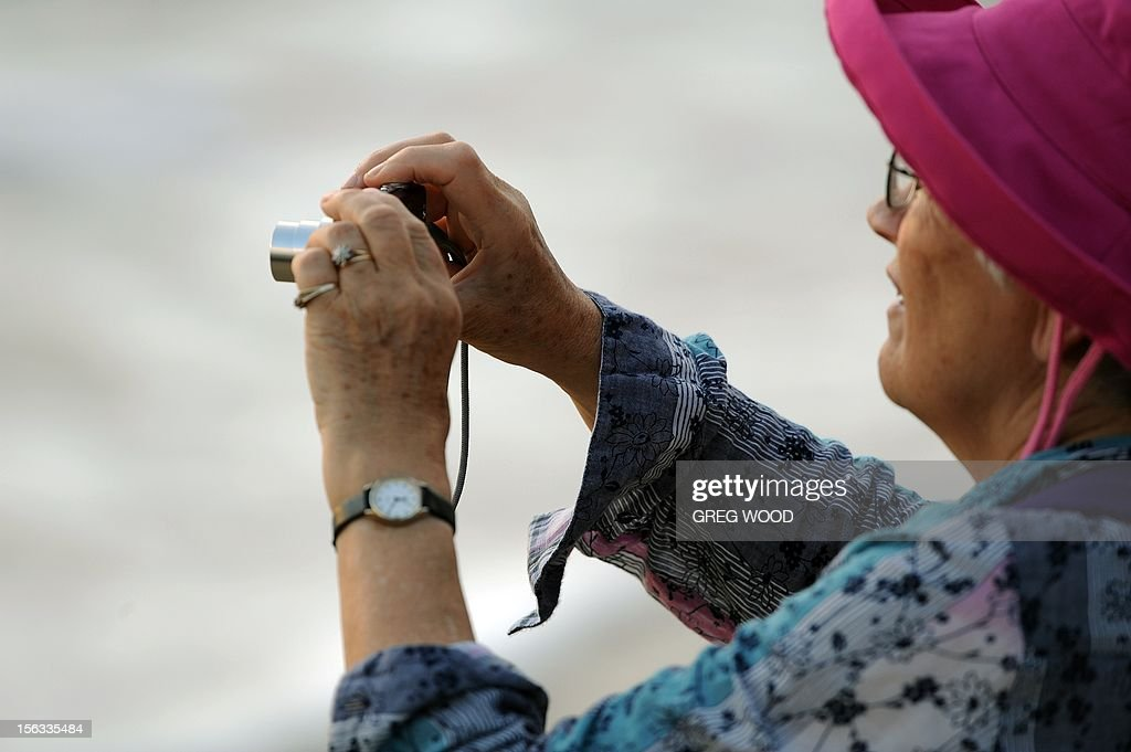 A woman takes a photograph as she waits for the sun to appear from behind clouds during the solar eclipse at Palm Cove in Australia's Tropical North Queensland on November 14, 2012. Eclipse-hunters have flocked to Queensland's tropical northeast to watch the region's first total solar eclipse in 1,300 years on November 14, which occurred as the moon passed between the earth and the sun, casting a shadow path on the globe and lasting for a maximum on the Australian mainland of 2 minutes and 5 seconds. AFP PHOTO / Greg WOOD