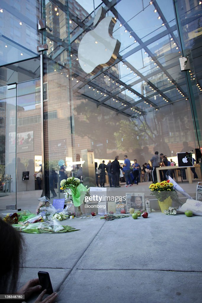 A woman takes a photograph at a memorial for Steve Jobs, co-founder and former chief executive officer of Apple Inc., outside an Apple store in New York, U.S., on Thursday, Oct. 6, 2011. Jobs, who built the world's most valuable technology company by creating devices that changed how people use electronics and revolutionized the computer, music and mobile-phone industries, died on Oct. 5. He was 56. Photographer: Stephen Yang/Bloomberg via Getty Images