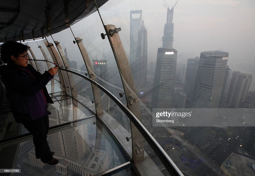 A woman takes a photograph from the observation deck on the Oriental Pearl Tower in the Pudong area of Shanghai, China, on Wednesday, Jan. 30, 2013. China's economic growth accelerated for the first time in two years as government efforts to revive demand drove a rebound in industrial output, retail sales and the housing market.Photographer: Tomohiro Ohsumi/Bloomberg via Getty Images
