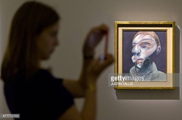 A woman takes a photograph in front of a canvas titled 'SelfPortrait' by British artist Francis Bacon with an estimate of £1015 Million GBP during a...