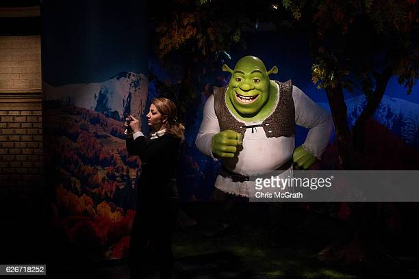 A woman takes a photograph in front of a waxwork figure of animated movie character Shrek on display at Turkey's first Madame Tussauds Wax Museum on...