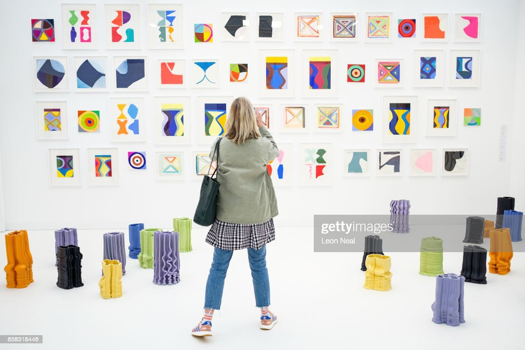 A woman takes a photograph of a display of work by Marina Adams at the Frieze Art Fair on October 6, 2017 in London, England. The annual event sees galleries showcase work by thousands of artists from around the world. The Frieze Art Fair runs from 5-8 October, 2017.