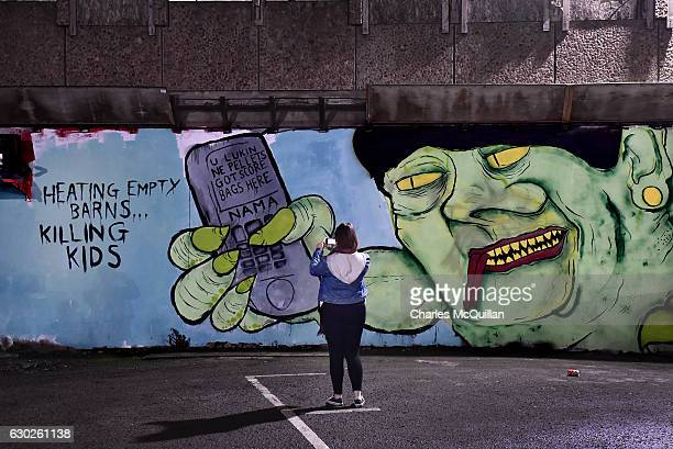 A woman takes a photograph of a freshly painted mural referencing the RHI crisis and Arlene Foster in a city centre car park on December 19 2016 in...