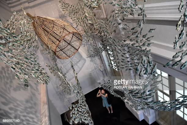 A woman takes a photograph of an art installation of marine life created from abandoned fishing nets by Erub Arts group artists from Australia's...