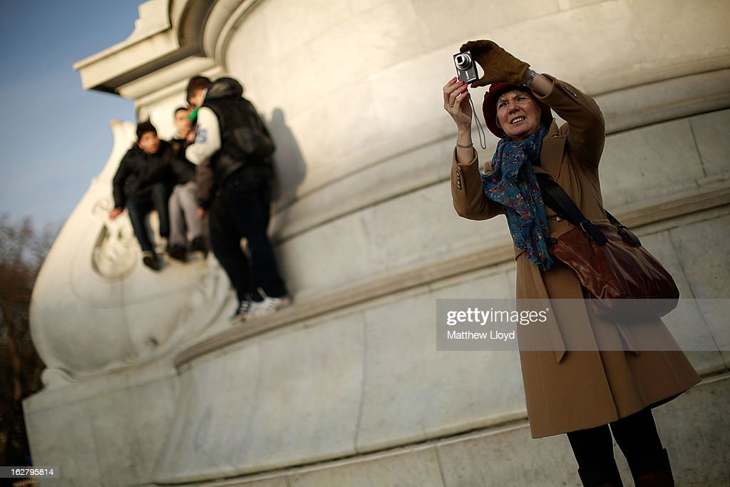 A woman takes a photograph of Buckingham Palace as youths climb on the Queen Victoria Memorial in the sunshine on February 27, 2013 in London, England. The Met Office has predicted a cold period at Easter.