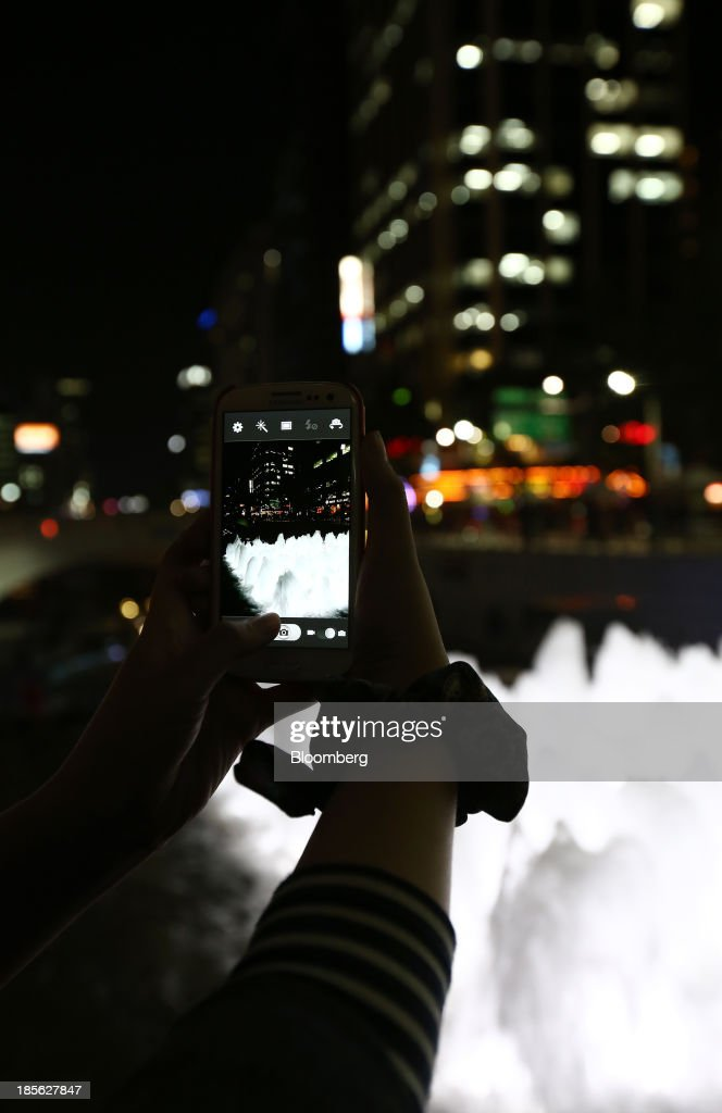 A woman takes a photograph of Cheonggye Stream using her Samsung Electronics Co. Galaxy S3 smartphone at night in Seoul, South Korea, on Tuesday, Oct. 22, 2013. Samsung Electronics is scheduled to release third-quarter earnings on Oct. 25. Photographer: SeongJoon Cho/Bloomberg via Getty Images