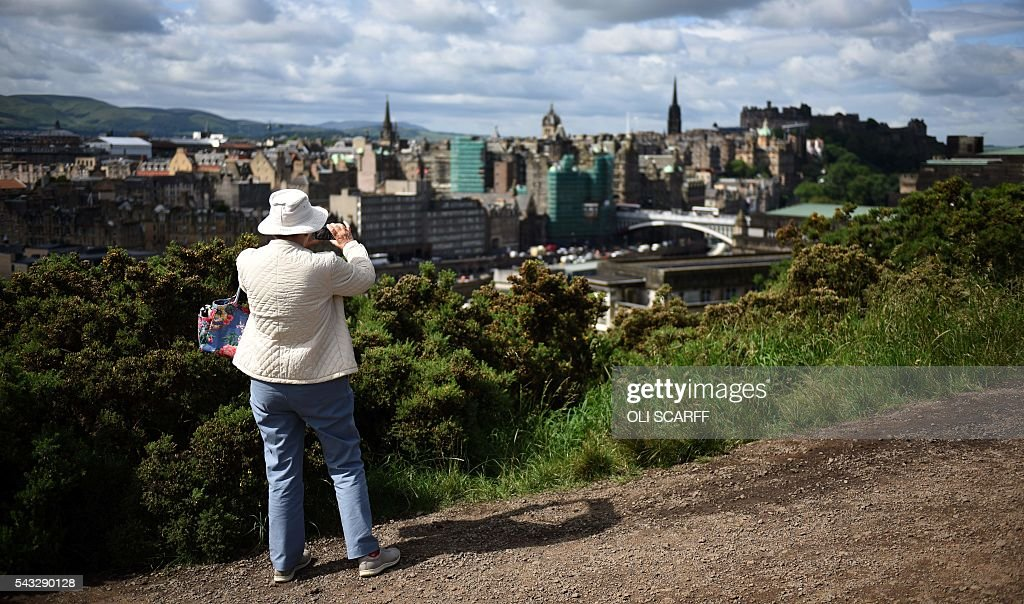 A woman takes a photograph of Edinburgh city centre from atop Calton Hill in Edinburgh, Scotland on June 27, 2016. British leaders battled to calm markets and the country Monday after its shock vote to leave the EU, while insisting London would be not rushed into a quick divorce. Britain's historic decision to be the first country to leave the 28-nation bloc has fuelled fears of a break-up of the United Kingdom with Scotland eyeing a new independence poll, and created turmoil in the opposition Labour party where leader Jeremy Corbyn is battling an all-out revolt. / AFP / OLI