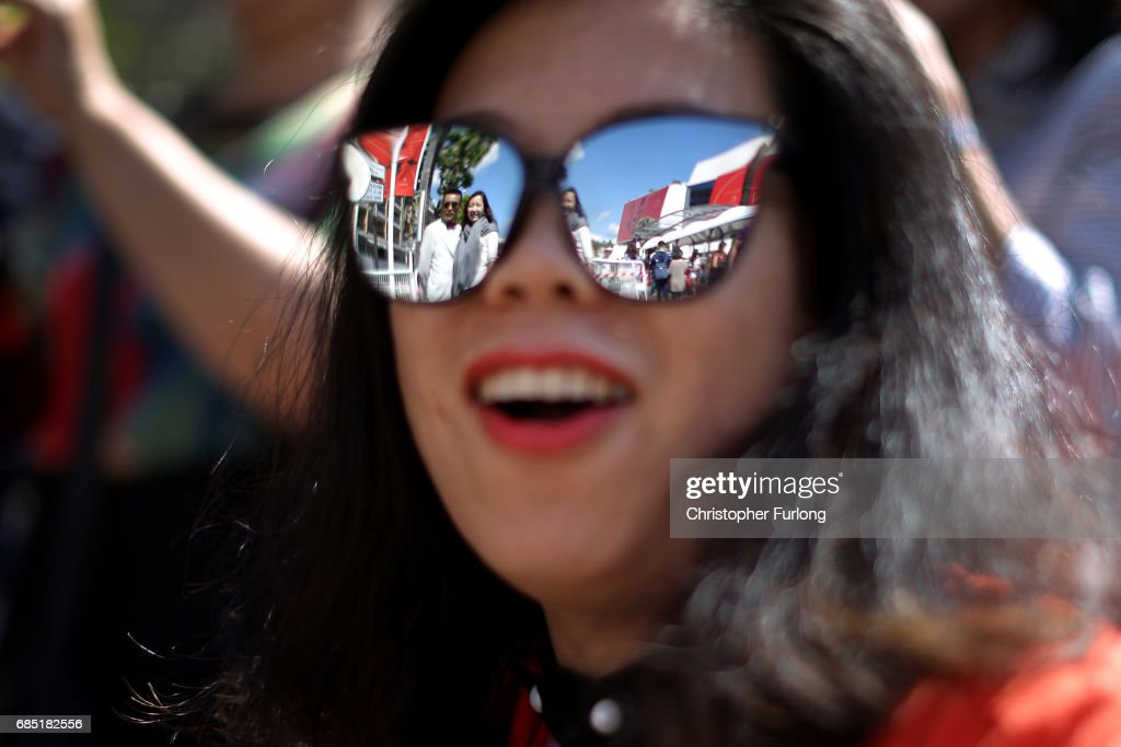 A woman takes a photograph of friends outside the Palais de festivals on the Boulevard de la Croisette during the Cannes Film Festival on May 19, 2017 in Cannes, France. Celebrities, fans and the movie world have descended on Cannes for this year's festival of the screen. For seventy years The Croisette Boulevard has always been the centre of athe place watch the rich and dandy and people from all walks of life to promenade.