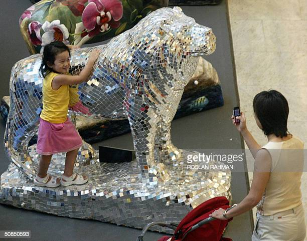A woman takes a photograph of her daughter with a mobile phone next to a unique series of lion sculptures displayed in a shopping mall in Singapore...