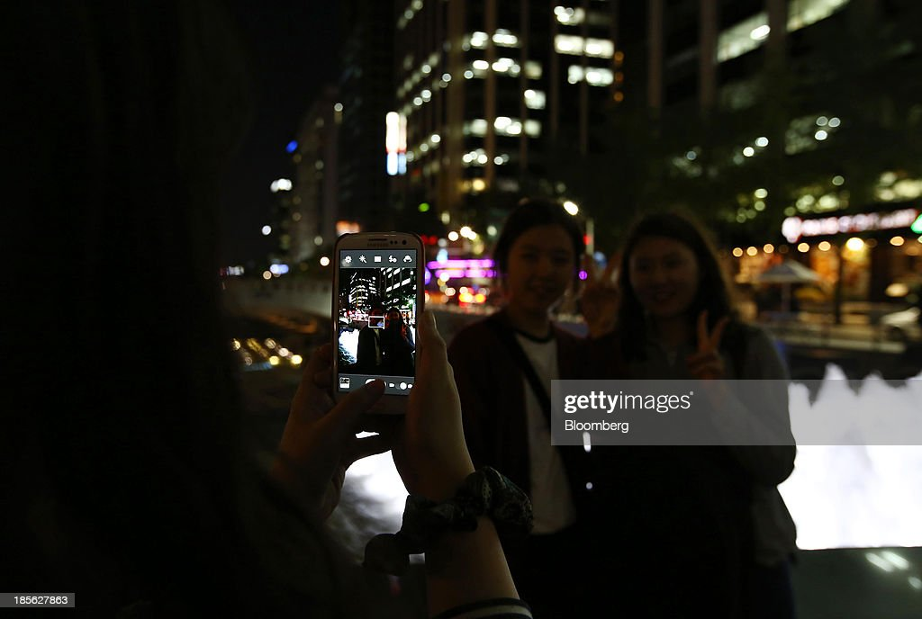 A woman takes a photograph of her friends using a Samsung Electronics Co. Galaxy S3 smartphone at night by Cheonggye Stream in Seoul, South Korea, on Tuesday, Oct. 22, 2013. Samsung Electronics is scheduled to release third-quarter earnings on Oct. 25. Photographer: SeongJoon Cho/Bloomberg via Getty Images