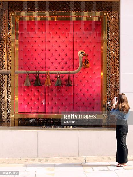 A woman takes a photograph of the window display of the Louis Vuitton shop on New Bond Street in Mayfair which is the most expensive avenue in Europe...