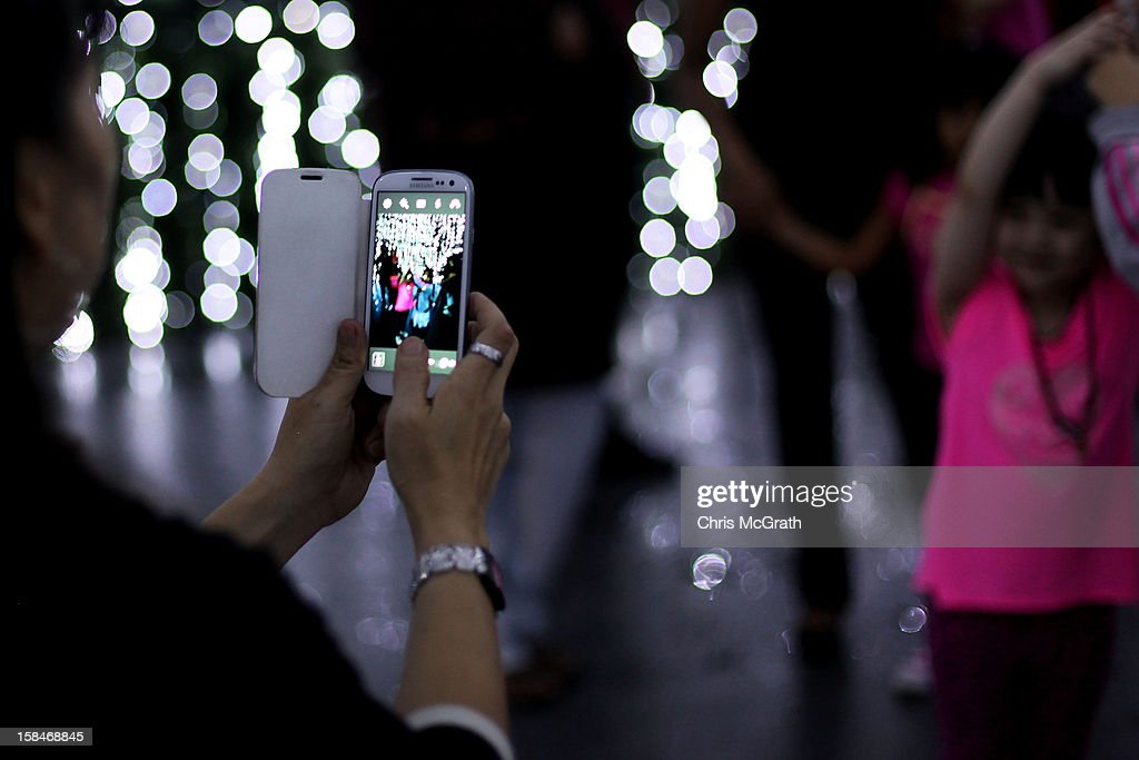 A woman takes a photograph on her smart phone outside a Christmas scene setup on Orchard road on December 17, 2012 in Singapore.