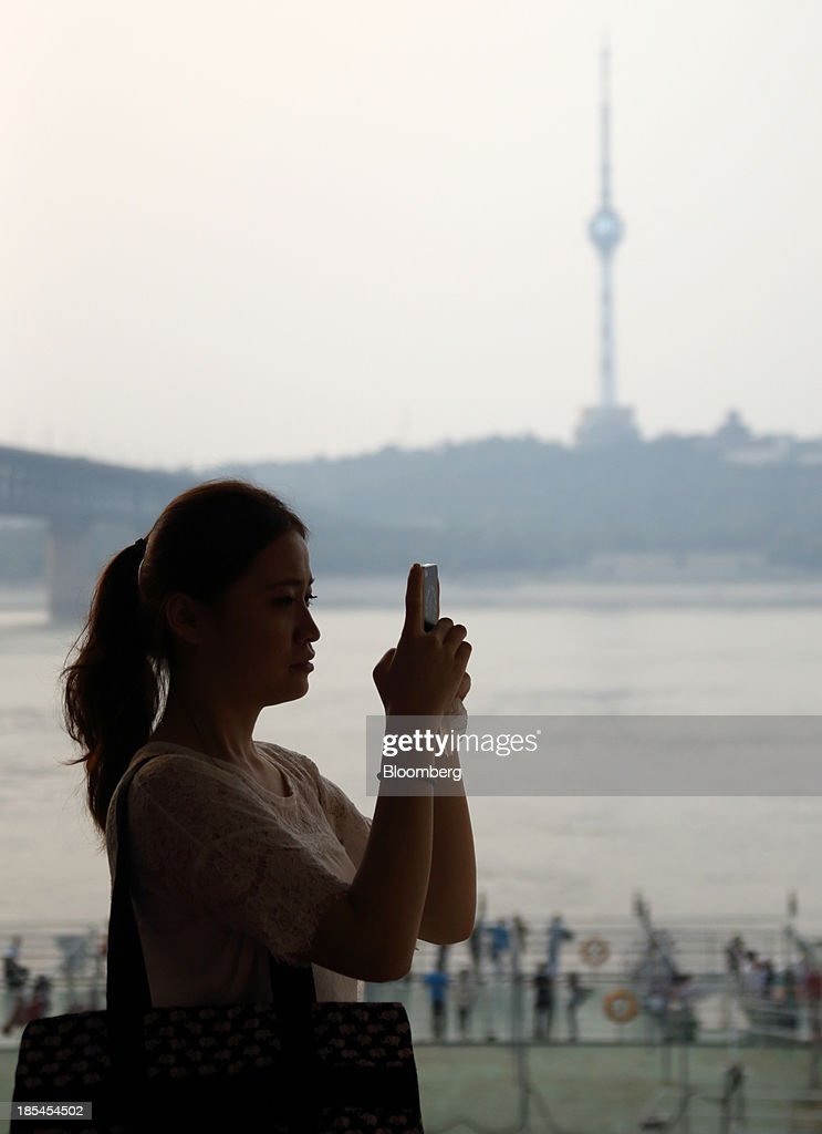 A woman takes a photograph using a smartphone beside the Chang Jiang river in Wuhan, China, on Sunday, Oct. 20, 2013. China's economic expansion accelerated to 7.8 percent in the third quarter from a year earlier, the statistics bureau said Oct. 18, reversing a slowdown that put the government at risk of missing its 7.5 percent growth target for 2013. Photographer: Tomohiro Ohsumi/Bloomberg via Getty Images