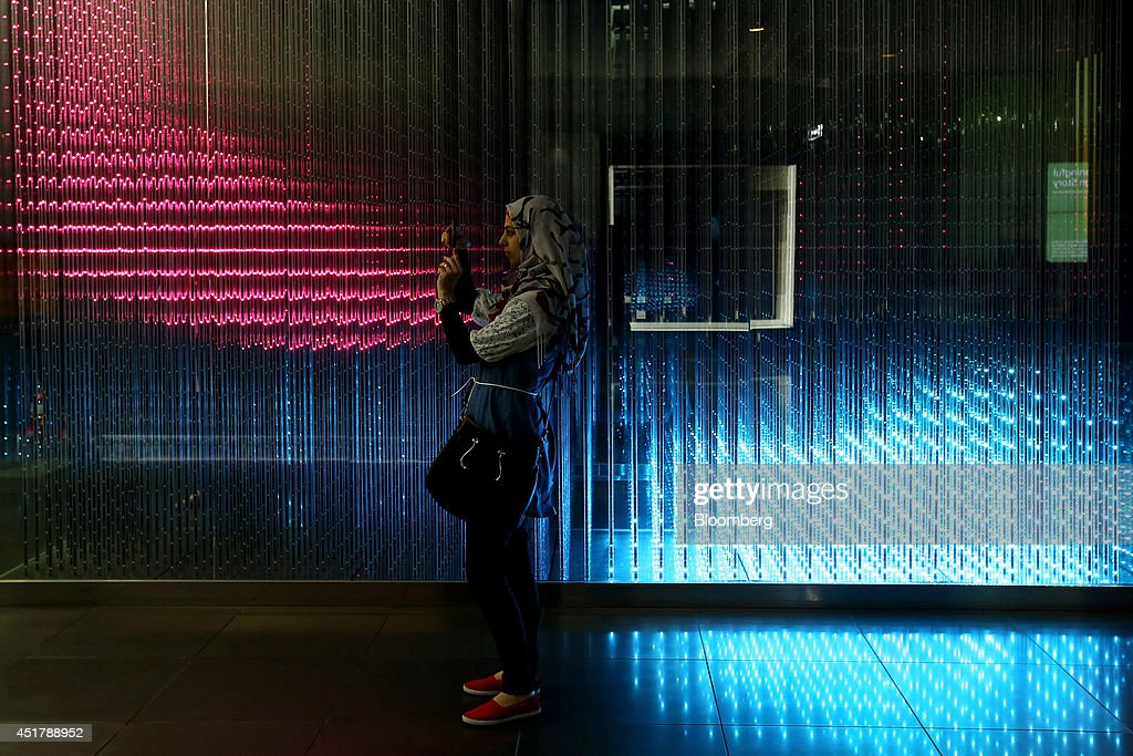 A woman takes a photograph using her mobile phone in front of a light emitting diode (LED) light wall at the Samsung Electronics Co. d'light showroom in Seoul, South Korea, on Monday, July 7, 2014. Samsung Electronics is scheduled to report operating profit and sales figures on July 8. Photographer: SeongJoon Cho/Bloomberg via Getty Images