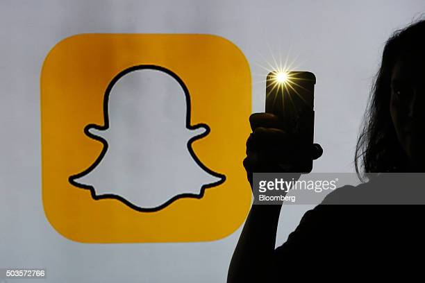 A woman takes a photograph with a camera whilst standing against an illuminated wall bearing Snapchat Inc's logo in this arranged photograph in...