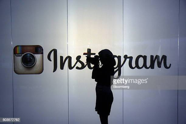 A woman takes a photograph with a digital slr camera whilst standing against an illuminated wall bearing Instagram Incs logo in this arranged...