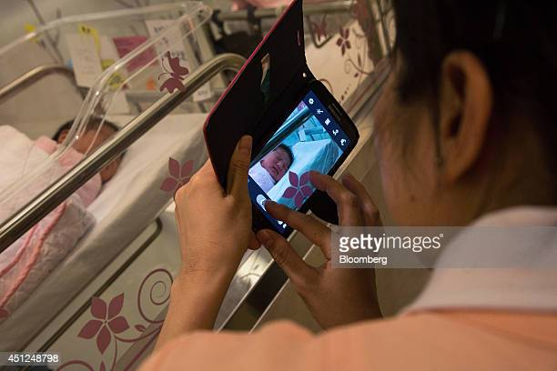 A woman takes a photograph with a mobile device of her friend's newborn baby in the nursery at Hong Kong Baptist Hospital in Hong Kong China on...