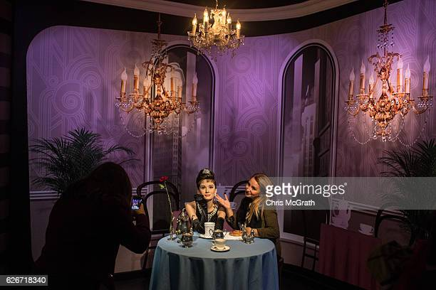 A woman takes a photograph with a waxwork figure of Audrey Hepburn on display at Turkey's first Madame Tussauds Wax Museum on November 30 2016 in...