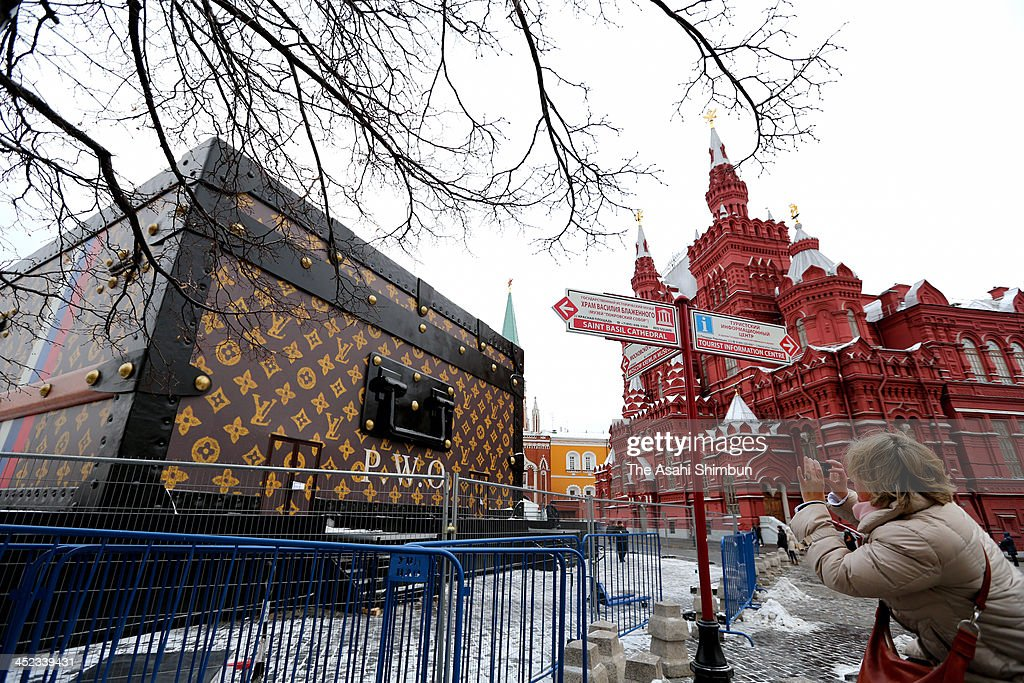 A woman takes a photographs of a giant Louis Vuitton suitcase-shaped pavilion installed in the middle of Moscow's Red Square, which will be dismantled, following a wave of public outrage and numerous demands for its removal on November 27, 2013 in Moscow, Russia.