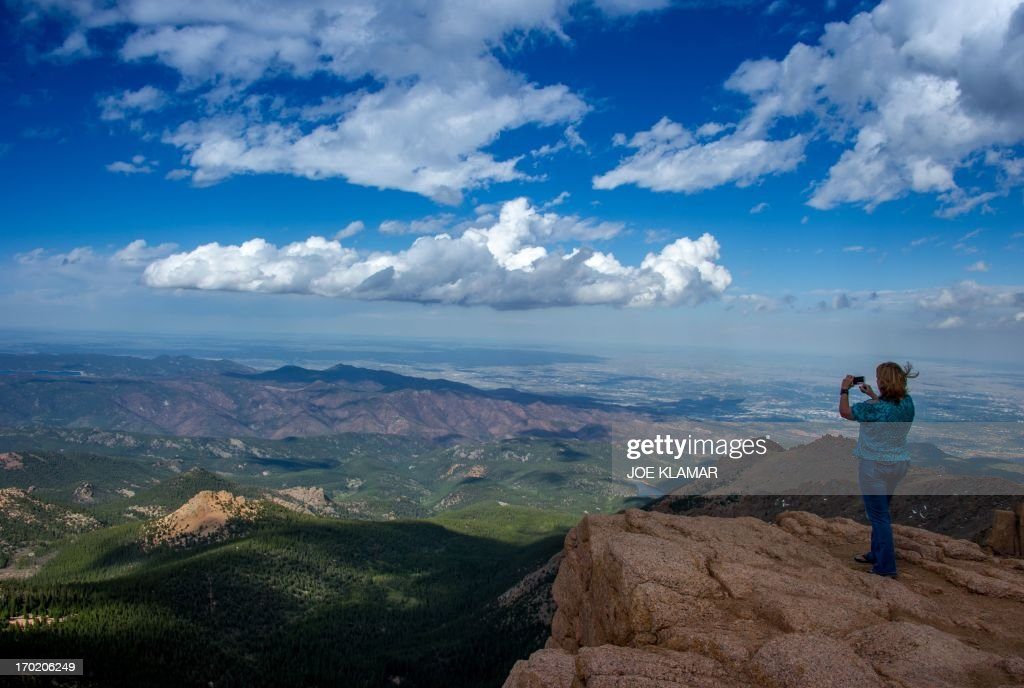A woman takes a picture at the top of Pikes Peak mountain in the Front Range of the Rocky Mountains within Pike National Forest 10 miles west of...