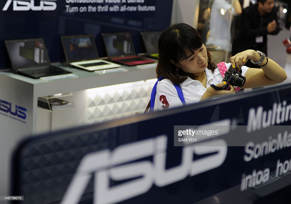 A woman takes a picture beside an ASUS logo during the Computex 2012 in Taipei on June 5, 2012. Computex is Asia's leading IT trade fair. AFP PHOTO / Sam YEH
