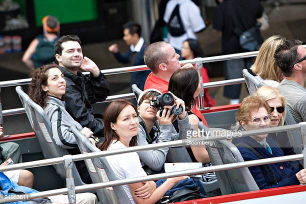 A woman takes a picture from the open top of a sight seeing bus traveling through Times Square in New York US on Thursday Sept 3 2009 Historically...