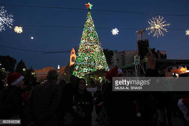 A woman takes a picture in front of a Christmas tree at the Manger Square near the Church of the Nativity revered as the site of Jesus Christ's birth...