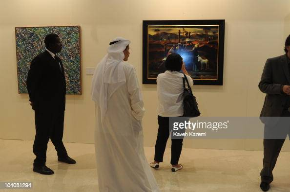 A woman takes a picture of a painting by an Egyptian artist which was sold moments earlier over 21 million Dollars in Christie's during an auction...