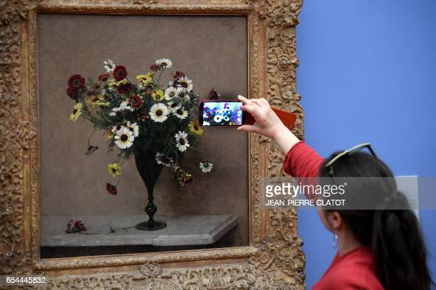 A woman takes a picture of a painting by French painter Henri FantinLatour and displayed during the retrospective exhibition 'FantinLatour A fleur de...