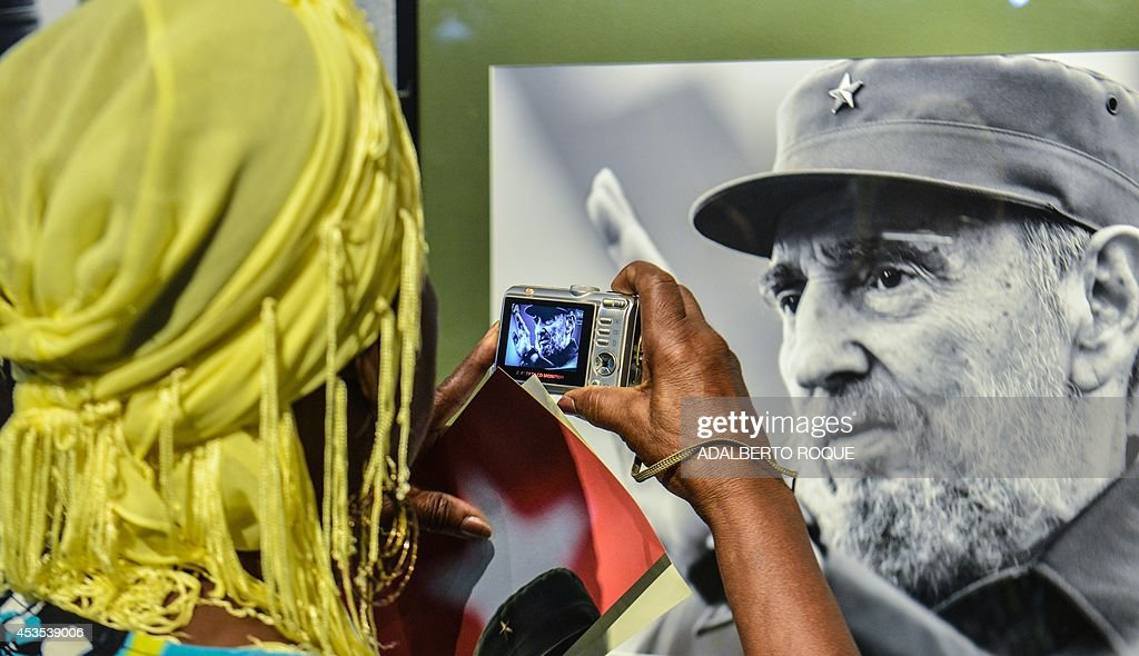 A woman takes a picture of a photo of former Cuban president Fidel Castro during the opening of a photography exhibition on him, on August 12, 2014 in Havana. Fidel Castro will turn 88 years old on Wednesday.