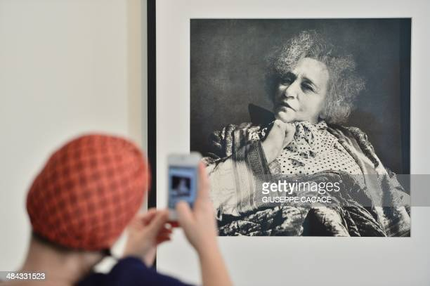 A woman takes a picture of a portrait of French writer Colette by photographer Irving Penn as part of the exhibition 'Irving Penn Resonance' at...