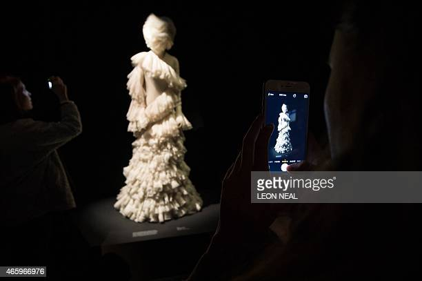 A woman takes a picture of a silk dress from 'The Widows of Culloden' Autumn / Winter 2006 collection during a press preview of Alexander McQueen's...