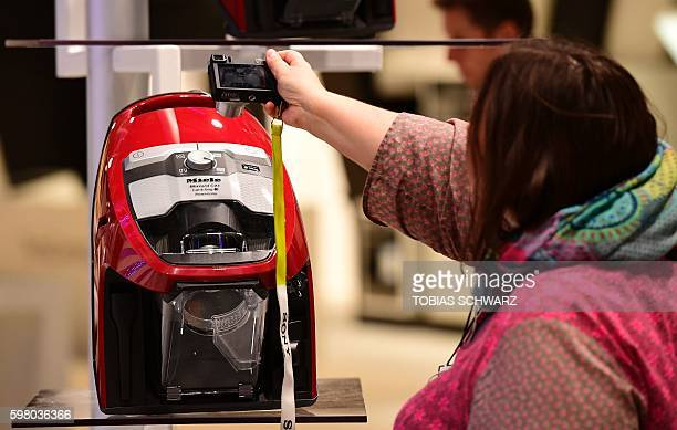 A woman takes a picture of a vacuum cleaner on the first press day to the IFA electronics trade fair in Berlin Germany on August 31 2016 The IFA is...