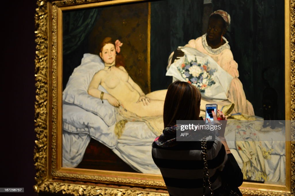 A woman takes a picture of Edouard Manet's 'Olympia' on April 23, 2013 in Venice, during the 'Manet Return to Venice' exhibition, which runs until 18 August 2013, at the Doge's Palace in Venice. Edouard Manet's 'Olympia' will be appearing alongside the Titan's 'Venus of Urbino' a masterpice of Renaissance and source of ispiration for the French artist.